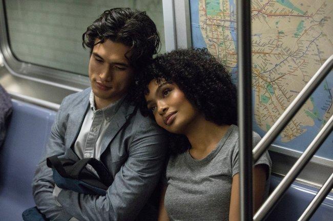 Daniel e Natasha, de O Sol Também É Uma Estrela, no metrô de Nova York; ele usa um terno cinza com camisa branca e segura a mochila preta no colo; ela usa uma camiseta cinza; os dois estão sentados nas cadeiras do vagão com um mapa na parede; Natasha está apoiada no ombro de Daniel e os dois estão com as cabeças encostadas e sorriem levemente olhando para frente