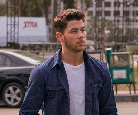 Nick Jonas na rua com jaqueta jeans