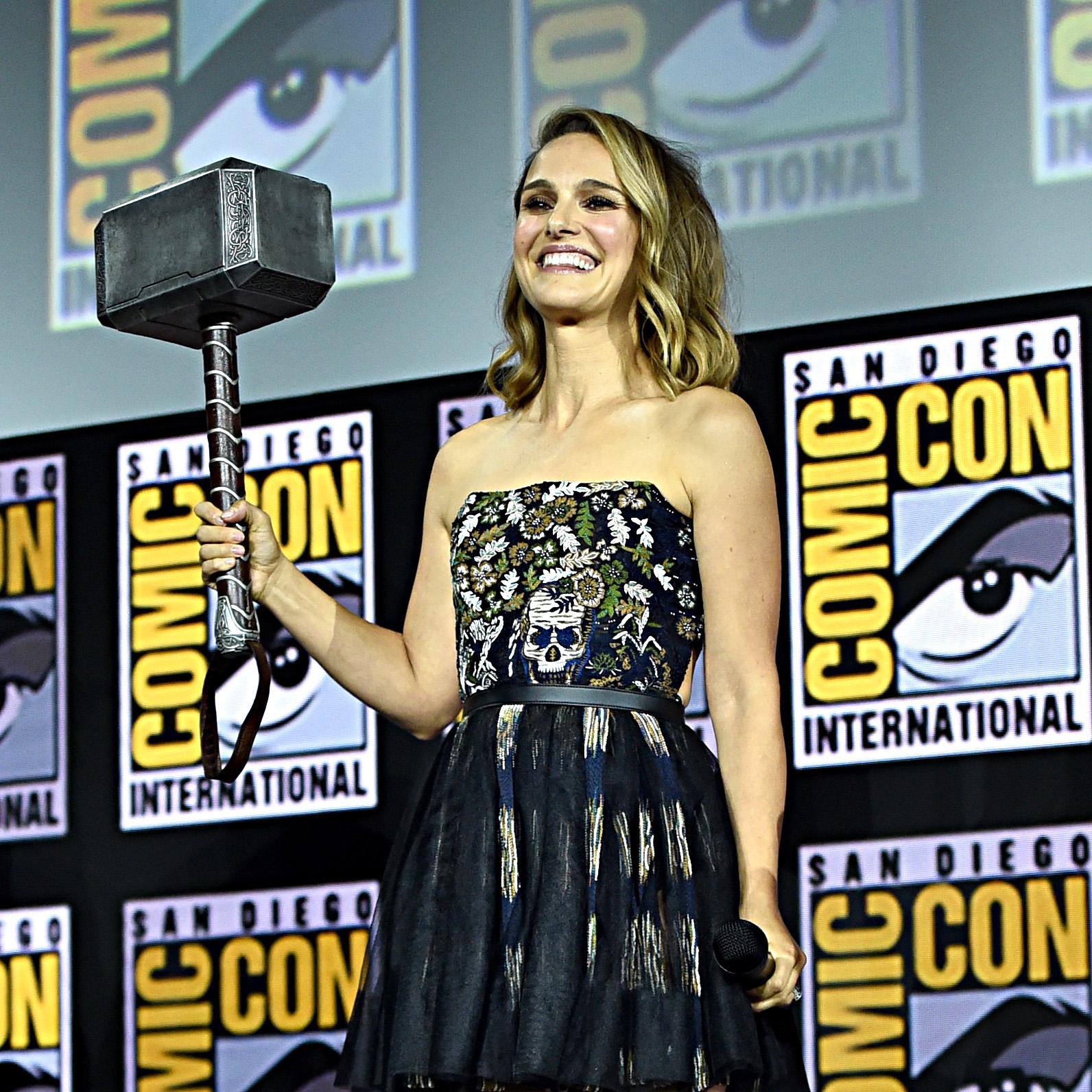 Natalie Portman no painel de Thor: Love and Thunder na San-Diego Comic Con 2019 segurando o martelo e sorrindo para o público