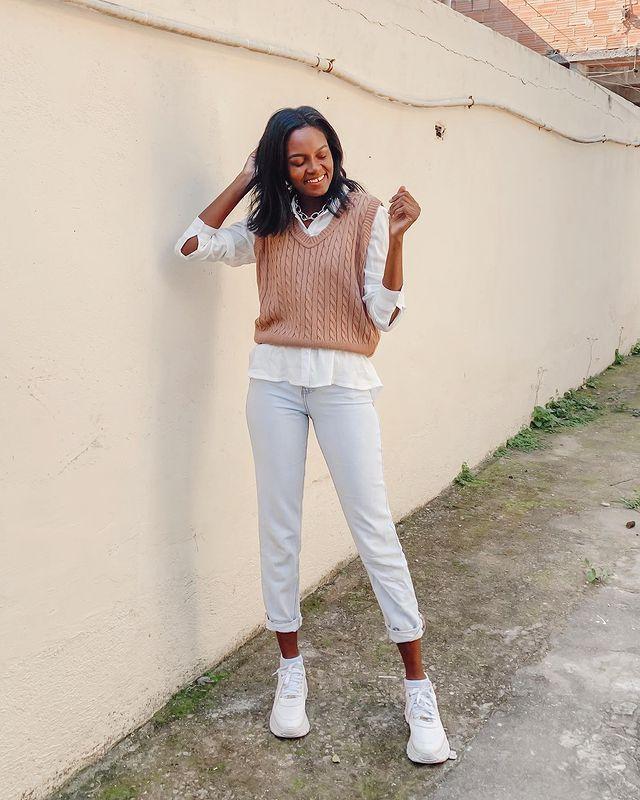 Garota usando colete de tricô marrom por cima de camisa branca, com calça jeans clara e tênis branco. Ela está sorrindo, com uma das mãos atrás do cabelo e o outro braço dobrado para cima.