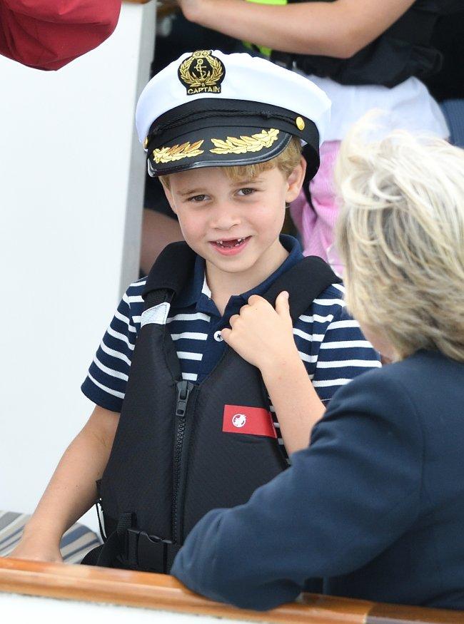 Prince George sorrindo e vestindo roupa que lembra estilo marinheiro e chapéu de marinheiro no evento esportivo King's Cup Regatta;