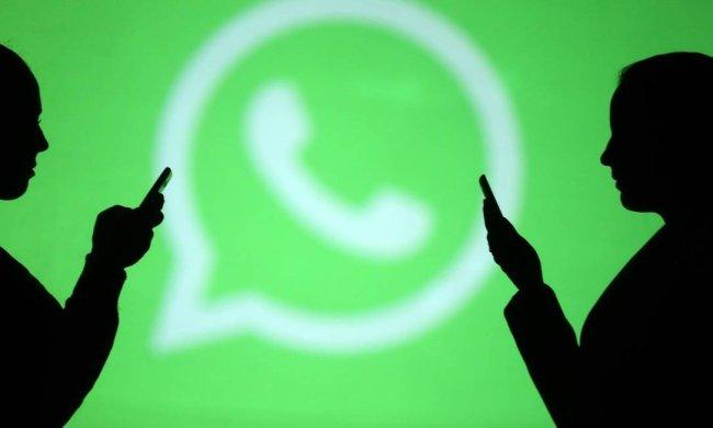 Duas pessoas seguram celulares e ao fundo está parede com o logo do Whatsapp