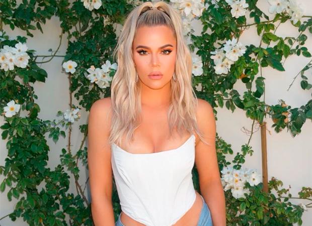 Khloé Kardashian posando para foto com uma blusa branca e expressão séria