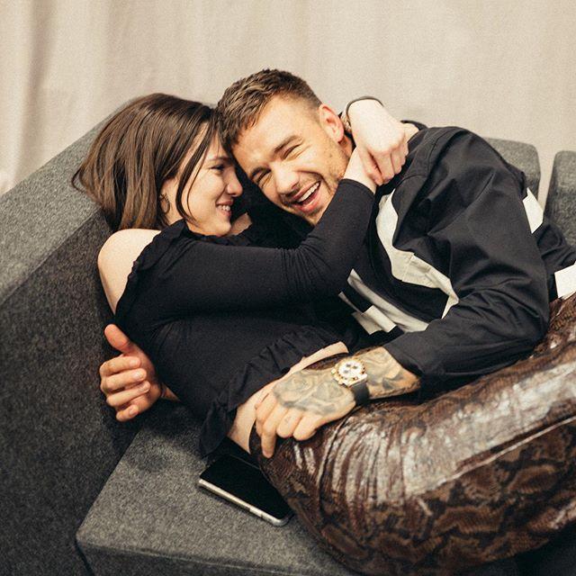 Liam Payne e Maya Henry deitados no sofá sorrindo; ela está abraçando o cantor pelo pescoço e encostando seu rosto no dele enquanto ele está rindo por cima dela