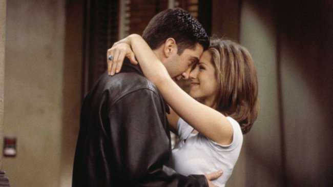 Cena de Ross e Rachel em Friends; os dois estão abraçados com os narizes se tocando e sorrindo um para o outro
