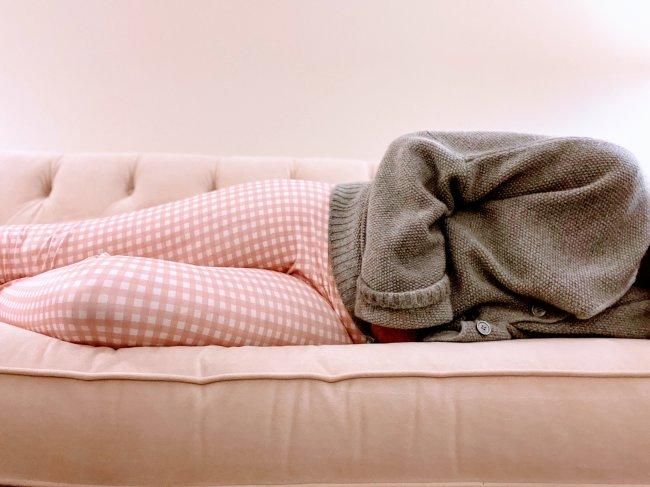 Garota com cólica menstrual deitada no sofá em posição fetal