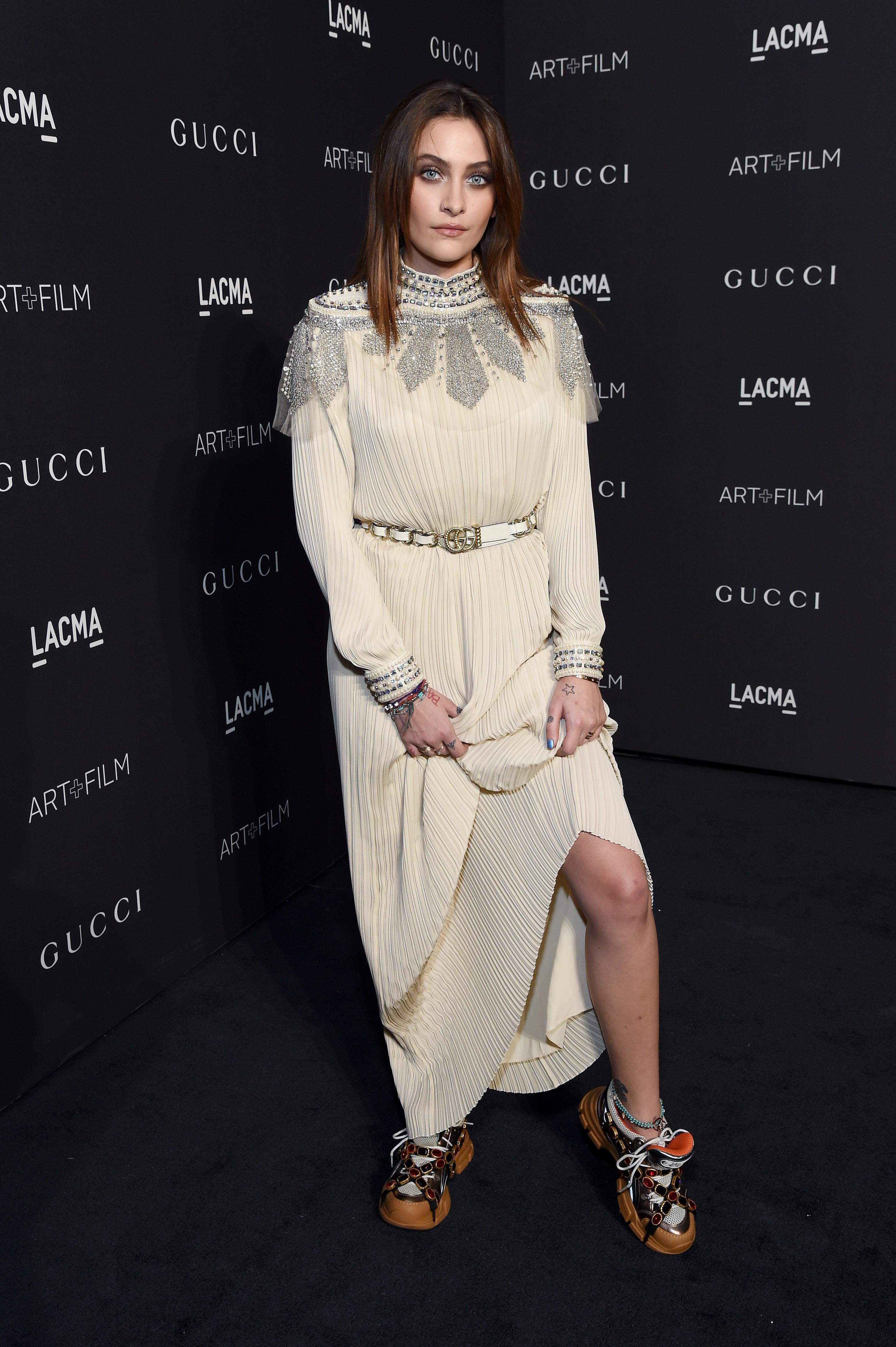 Foto de Paris Jackson no tapete vermelho no Museu de Arte do Condado de Londres. Ela usa um vestido branco com detalhes em diamante e tênis da Gucci. Ela olha para a câmera e não sorri.