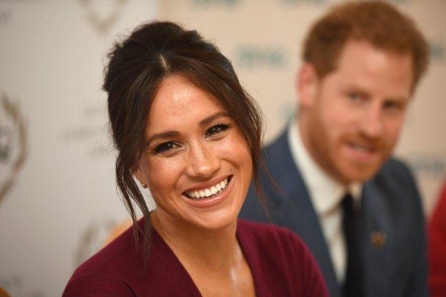 Meghan Markle sorrindo para foto; ela está com o cabelo preso e a franja divida ao meio com pontas soltas; ela usa uma roupa vinho