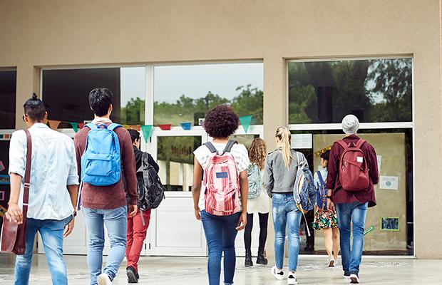 A imagem mostra várias pessoas, com mochilas nas costas, viradas de costas e caminhando em direção a entrada do que parece ser uma escola.