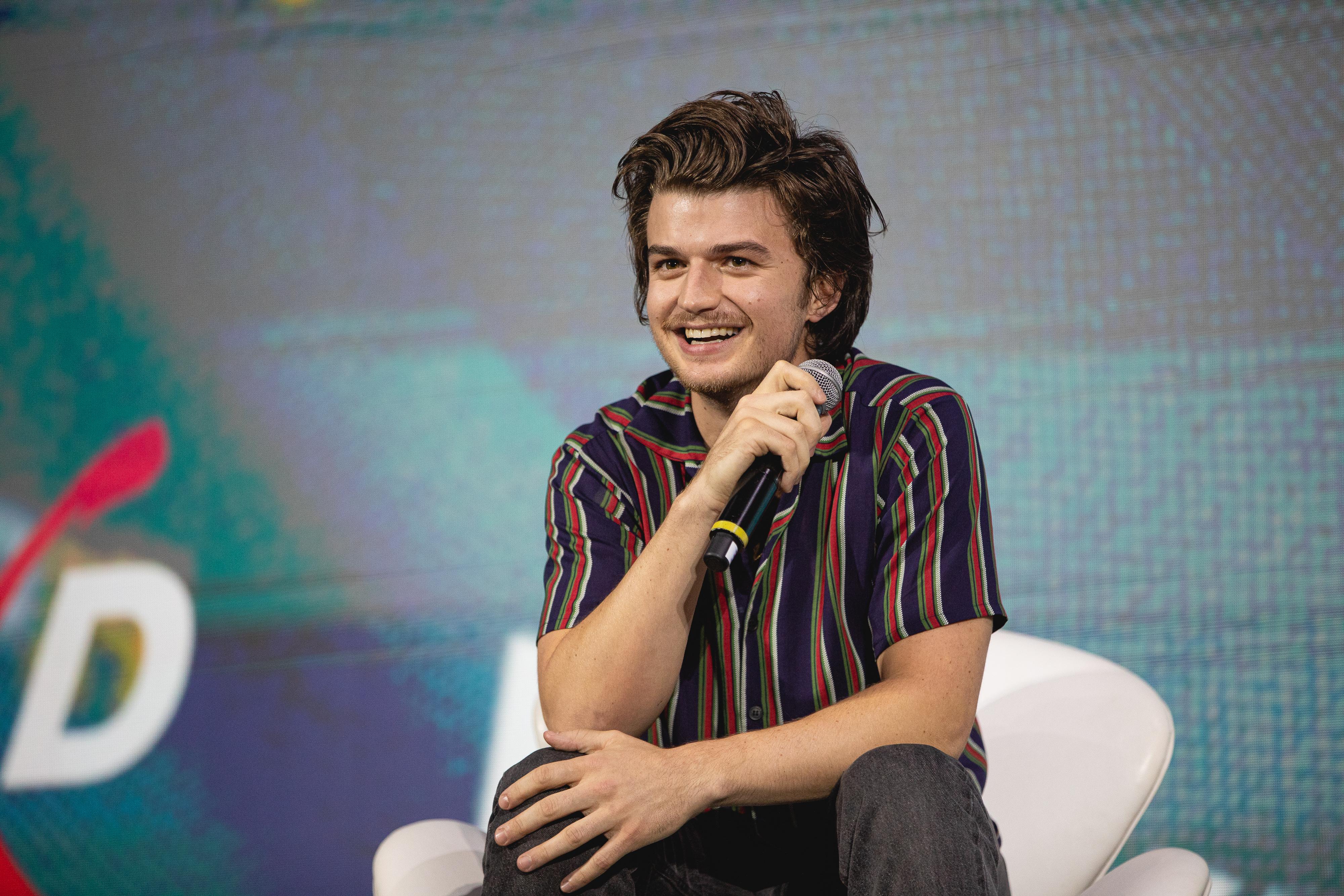 Joe Keery sentado em cadeira branca no palco do painel de Free Guy, na CCXP 2019, em São Paulo; o ator segura o microfone com uma das mãos enquanto a outra repousa em seu joelho, ele sorri observando o público e usa uma camisa listrada em tons de azul escuro, vermelho e verde