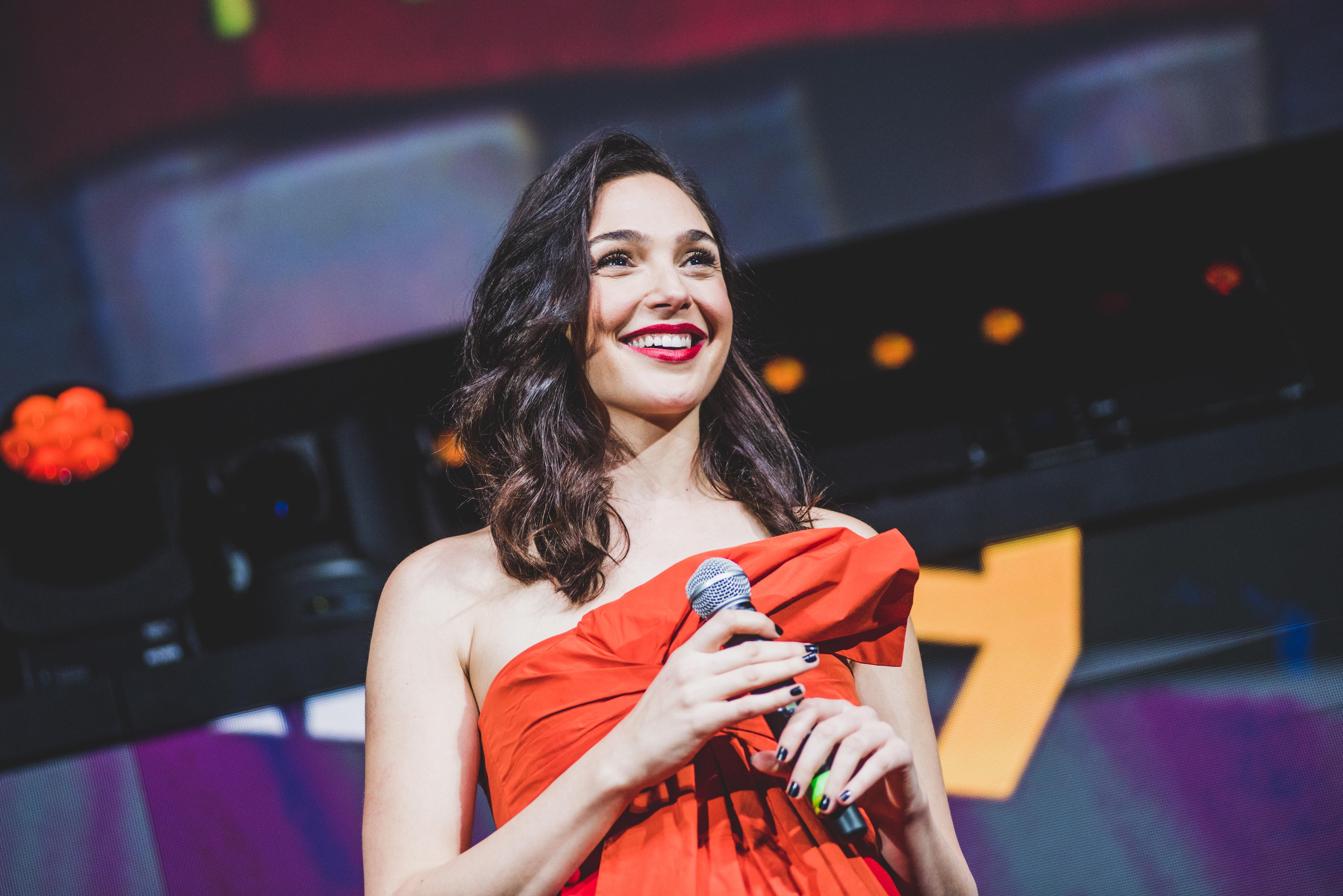 Gal Gadot segurando microfone enquanto olha para o público em painel da CCXP19, em São Paulo, com roupa vermelha e cabelo solto