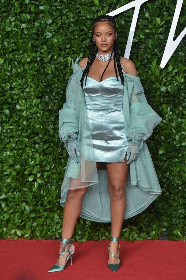 Rihanna posando com trança, vestido azul e casado ca mesma cor. Em tapete vermelho com fundo verde. Sua expressão é séria.