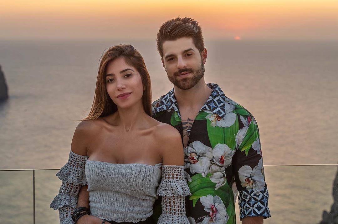 Foto de Romana e Alok; ela usa uma blusa off shoulder branca com babados na manga; ele usa uma camisa estampad em tpns de verde, preto e branco e está com a mão na cintura da médica; os dois sorriem levemente