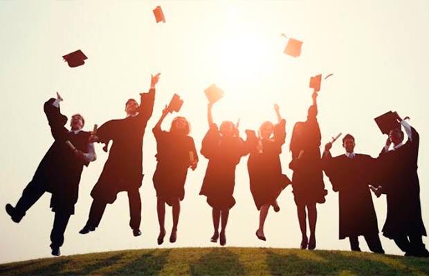 Imagem de estudantes jogando seus chapéus de formando ara o alto.