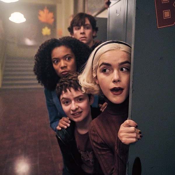 Foto dos bastidores de O Mundo Sombrio de Sabrina - Parte 3 com os personagens se escondendo atrás da porta de um armário da escola