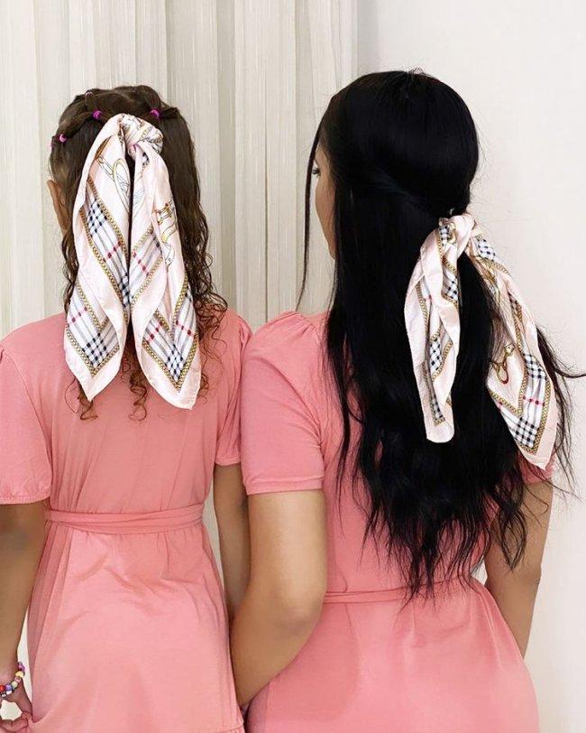 Mãe e filha de costas, usando vestido rosa da mesma tonalidade, a mãe está ajoelhada ao lado da filha, as duas usam lenços no cabelo.