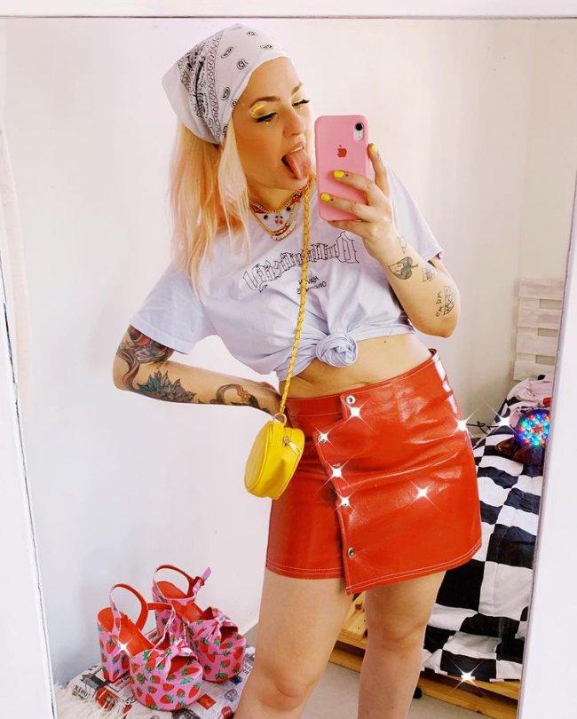 Jovem posando para foto com celular rosa a mostra, com o corpo levemente inclinado, mostrando a lingua, usando a camiseta branca amarrada na barriga, uma saia vermelha de couro e uma bolsa lateral amarela e pequena.