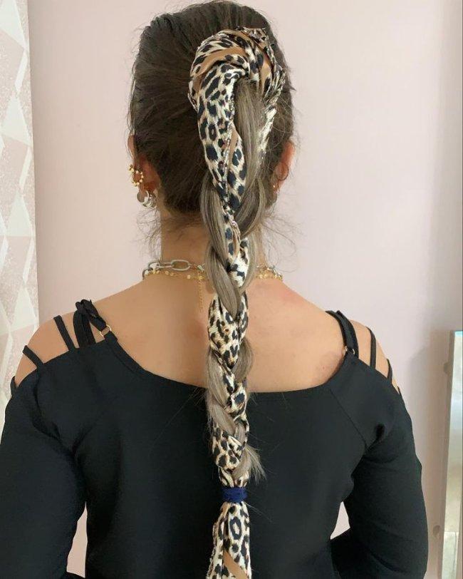 Mulher de costas com trança no cabelo, e lenço entrelaçado na trança. Usando blusa preta com abertura no ombro.