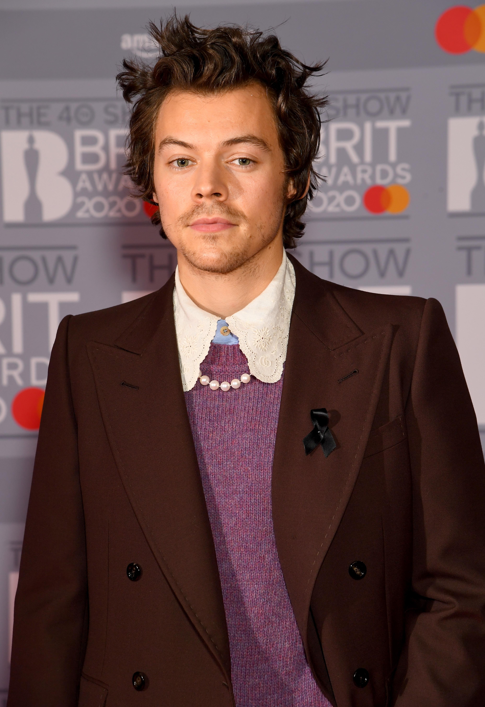 Harry Styles usando terninho da Gucci no BRIT Awards com expressão facial séria, suéter roxo e gola da camisa branca aparente