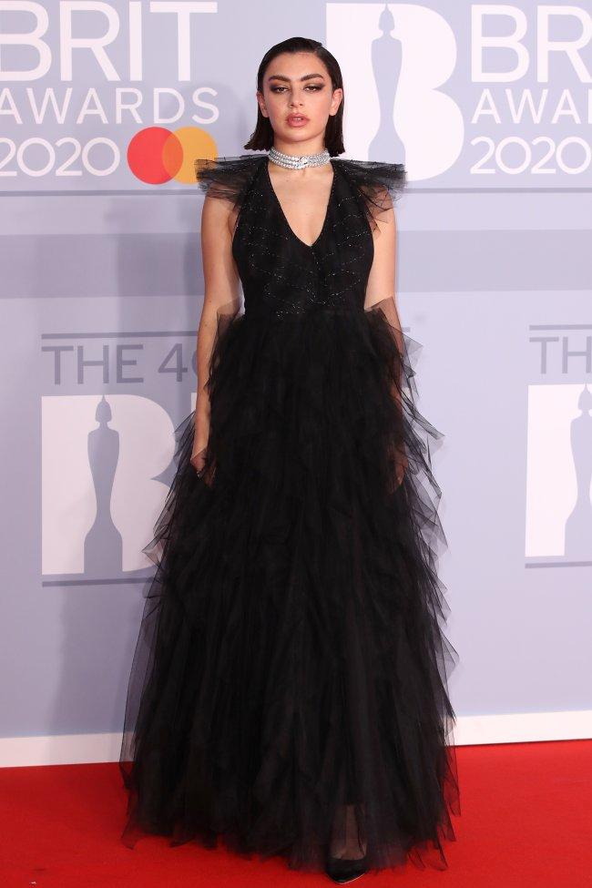 Charli XCX posando para foto no red carpet do BRITs 2020 usando um vestido preto com saia volumosa e um colar brilhante prata