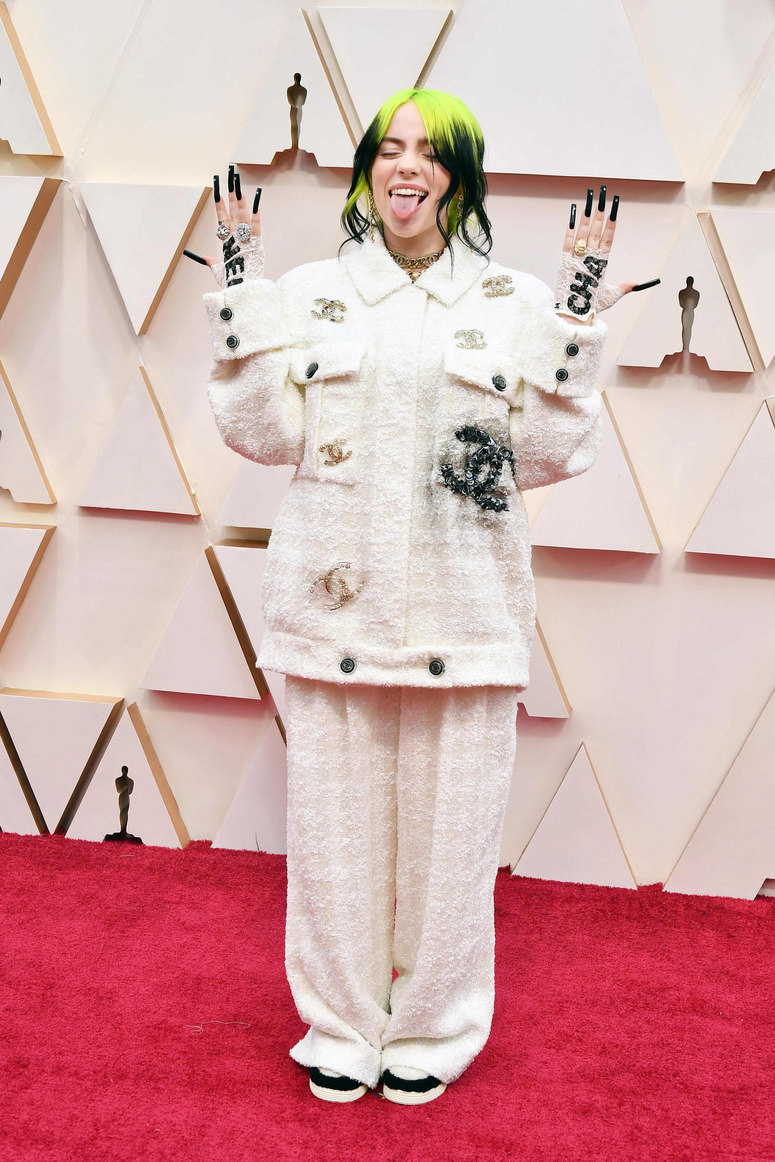 Foto da Billie Eilish no tapete vermelho do Oscar em 2020. Ela usa um conjunto da Chanel branco e tênis. Ela sorri e mostra a língua para a foto.