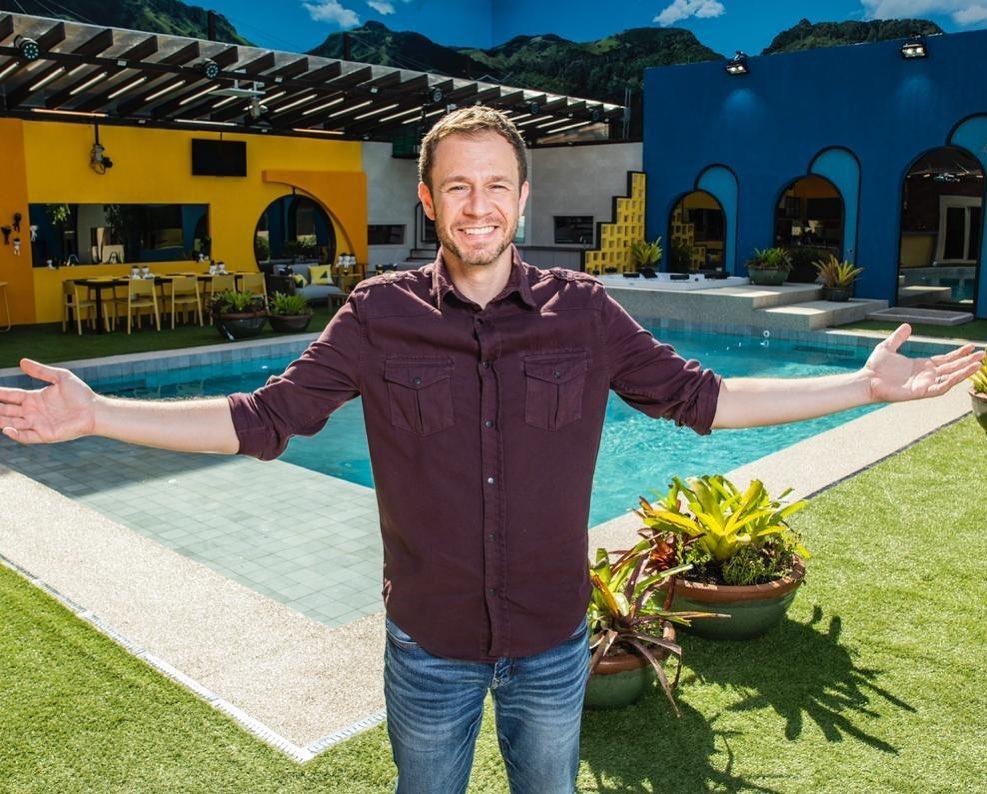 Tiago Leifert na casa do BBB20 com os braços abertos sorrindo na frente da piscina