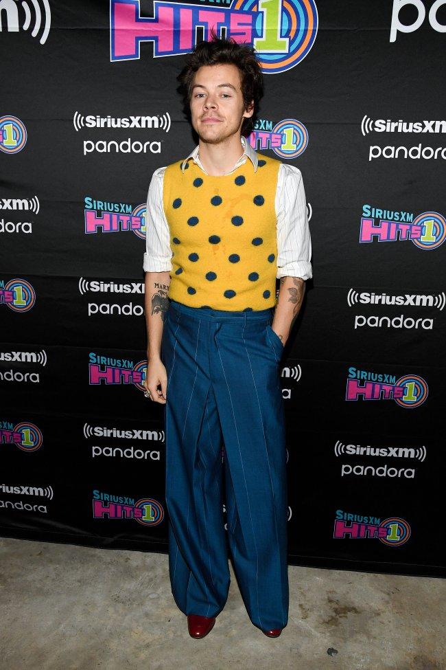 Harry Styles usando colete amarelo de poá por cima de uma camisa branca