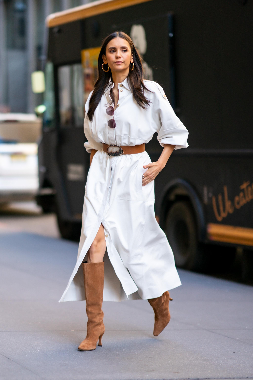 Nina Dobrev usando vestido branco de botões frontais com cinto marrom e bota marrom de camurça e comprimento abaixo do joelho