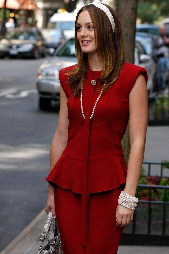 Blair posando de vestido vermelho usando colar e tiara.