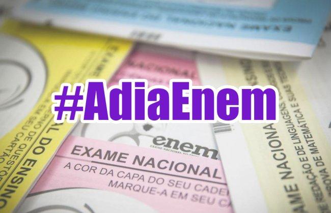 A imagem mostra alguns pedaços de vários cadernos de prova do Enem, nas cores rosa, amarelo, azul e branco, e a hashtag AdiaEnem escrita em roxo, em cima da foto.