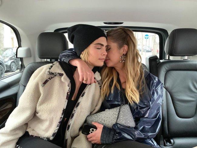 Ashley Benson e Cara Delevingne no carro abraçadas; a atriz está com o rosto escondido no pescoço de Cara e o braço em volta da modelo que tem os olhos fechados