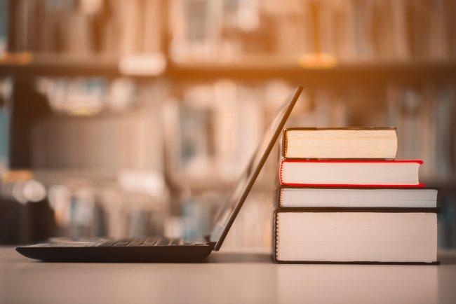 A imagem mostra um computador virado de lado em uma mesa e apoiado em uma pilha de quatro livros. Ao fundo da imagem, levemente desfocada, é possível ver uma estante com vários livros.
