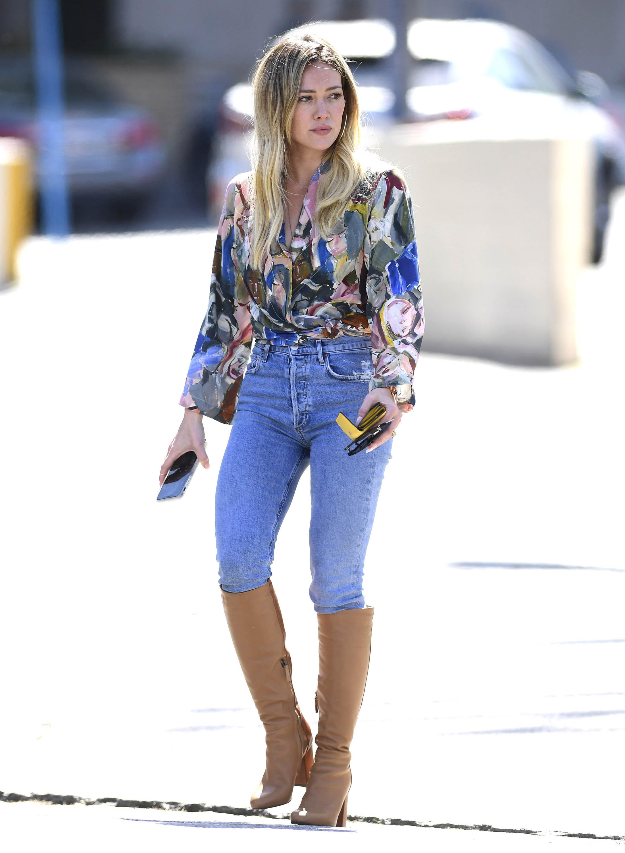 Hilary Duff usando bota marrom abaixo do joelho por cima de calça jeans e uma camisa estampada
