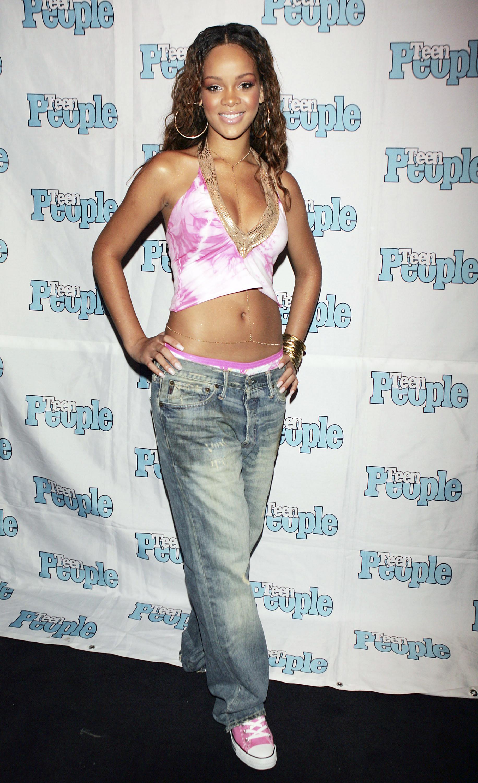 Rihanna em 2005. Ela está usando top cropped tie-dye rosa, calça jeans de cintura baixa e tênis All Star rosa. Ela também está usando o cinto dourado que era tendência nos anos 2000. Ela está sorrindo e com as duas mãos na cintura.