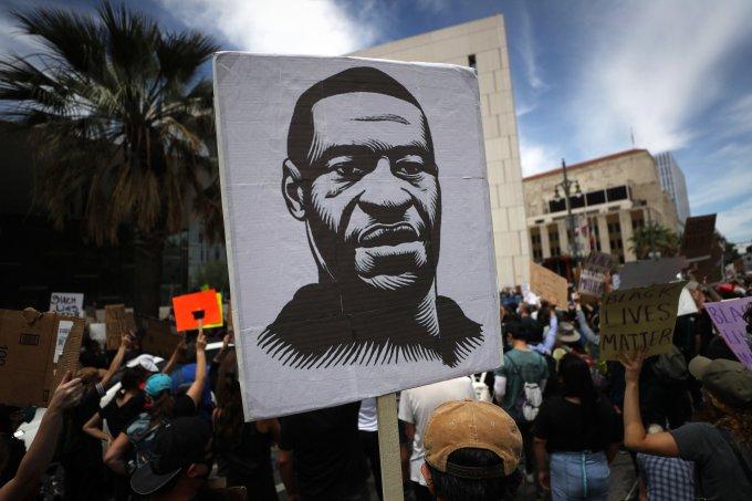 Manifestante segura placa com imagem de George Floyd