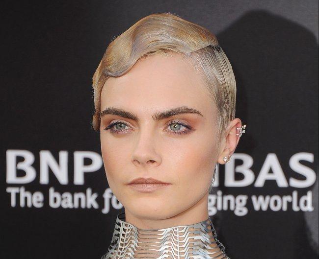Cara Delevingne posando para foto com o cabelo penteado com gel; a expressão da modelo é séria e ela usa acessórios prateados