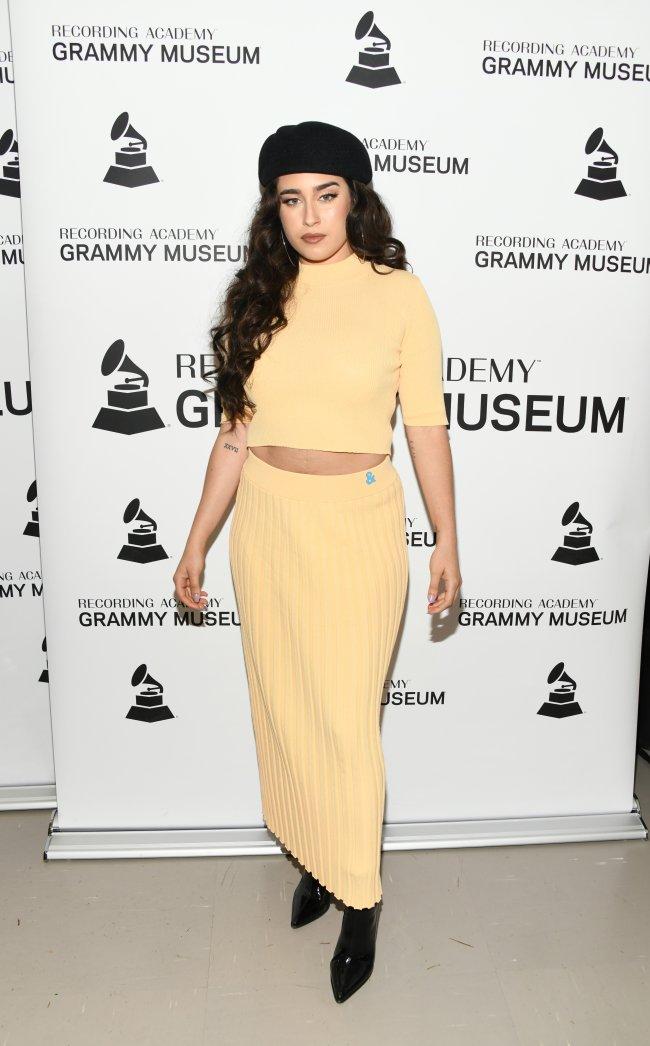 Lauren Jauregui com boina e conjunto amarelo em carpet do Grammy Museum