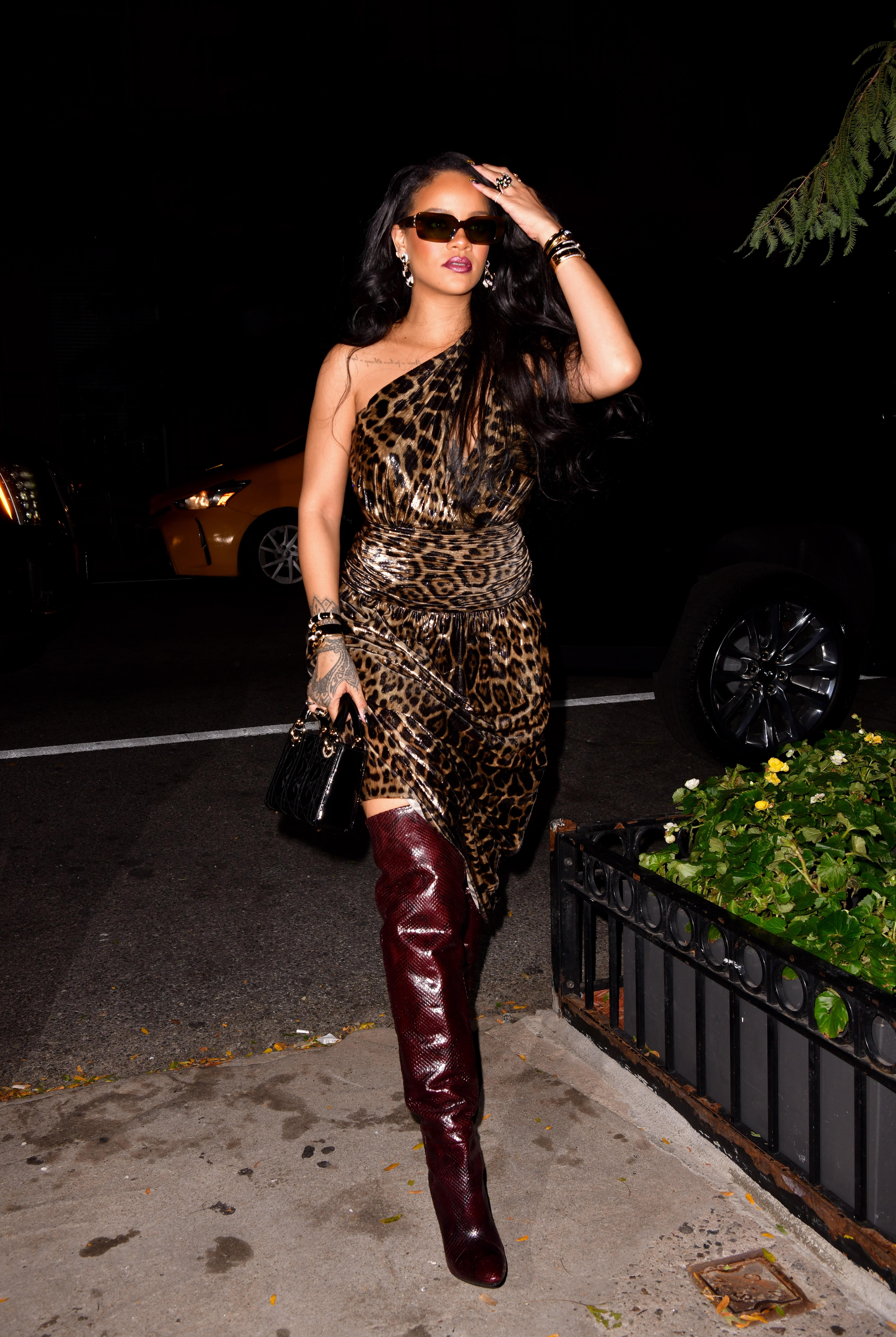 Rihanna ficou usando vestido de um ombro só com estampa de oncinha, bota over the knee bordô com estampa de cobra e óculos de sol de armação retangular. Ela está com uma das mãos no cabelo e a outra segurando uma bolsa preta.