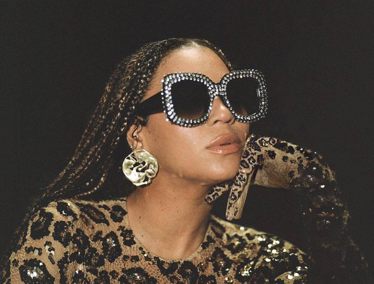 Beyoncé com a mão rosto e óculos escuro