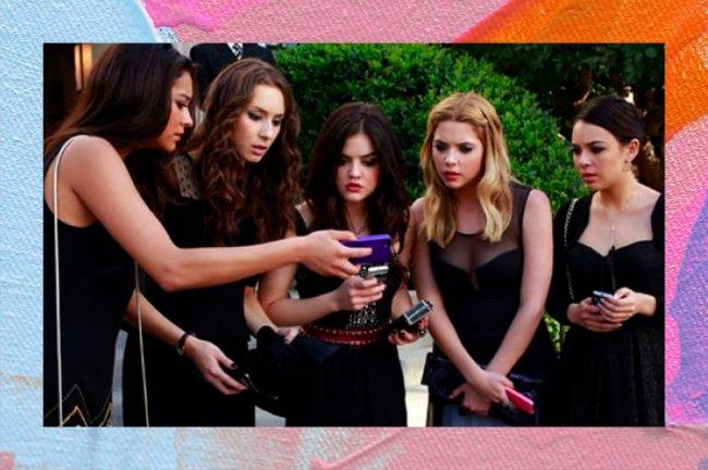 Atrizes de Pretty Little Liars, vestindo roupas pretas, estão em roda olhando assustadas para um celular