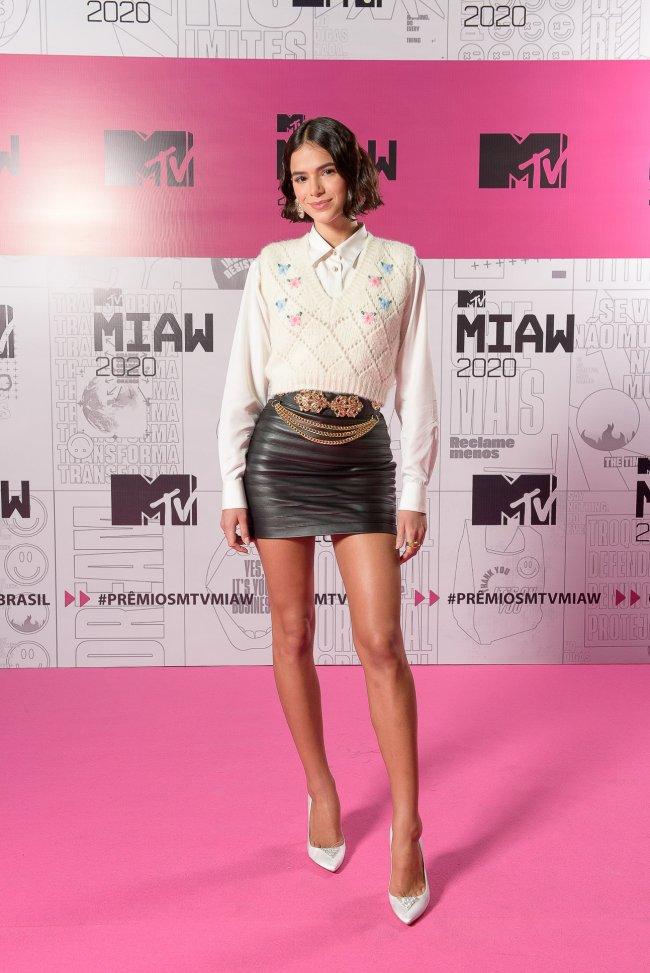 Bruna Marquezine usando saia de couro com camisa branca e colete de tricô por cima no MTV Miaw 2020