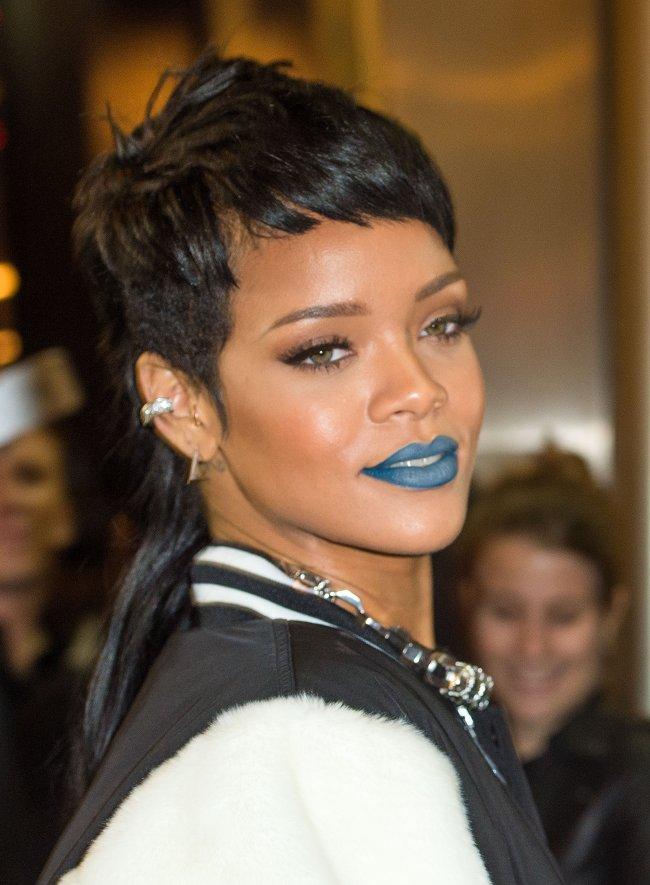 Rihanna posando com batom azul, olhando para o lado sorridente, com camisa preta e branca.