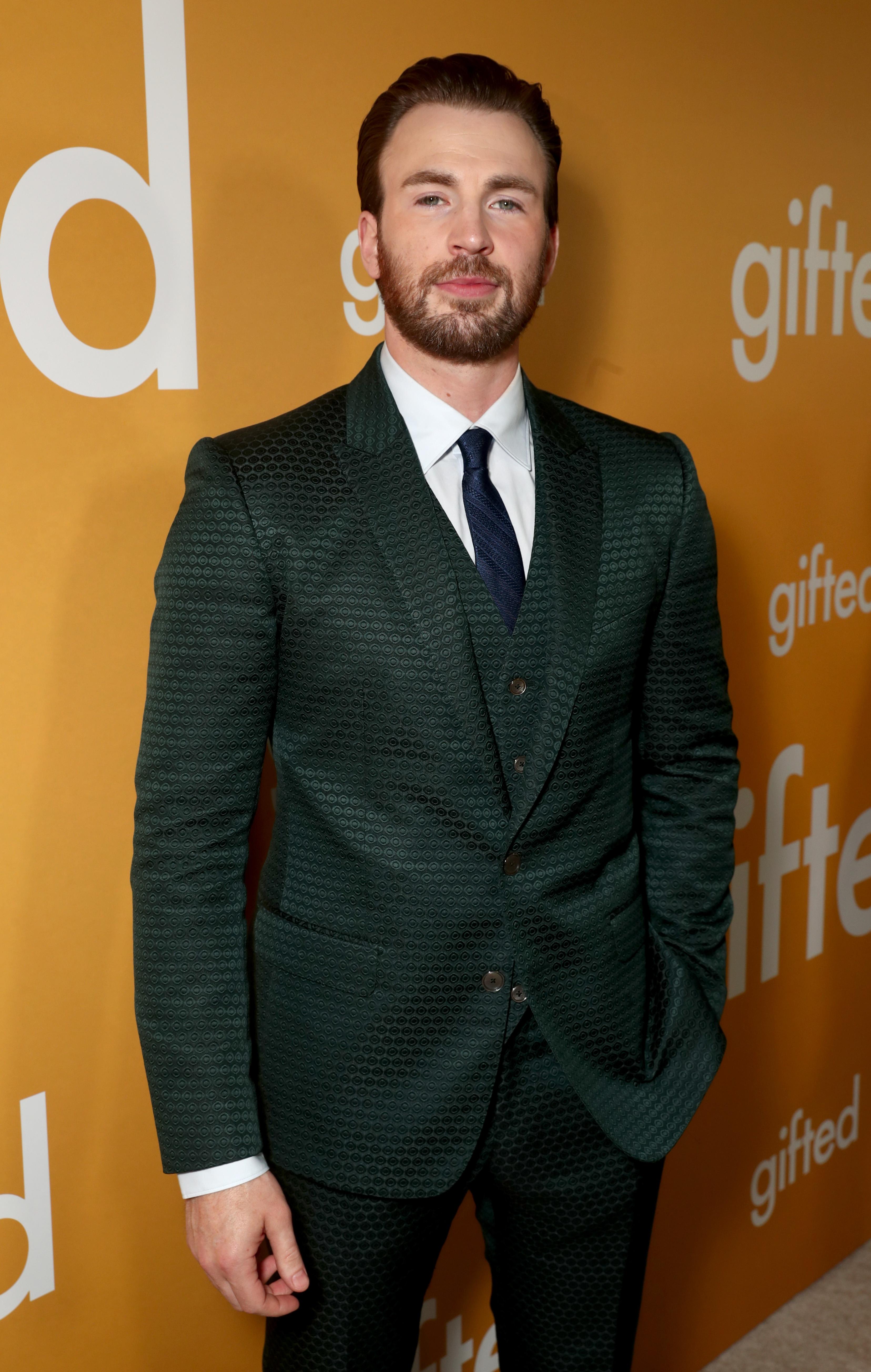 Chris Evans posando para foto em carpet com terno em tom de verde escuro e camisa branca; o ator sorri levemente com uma das mãos no bolso