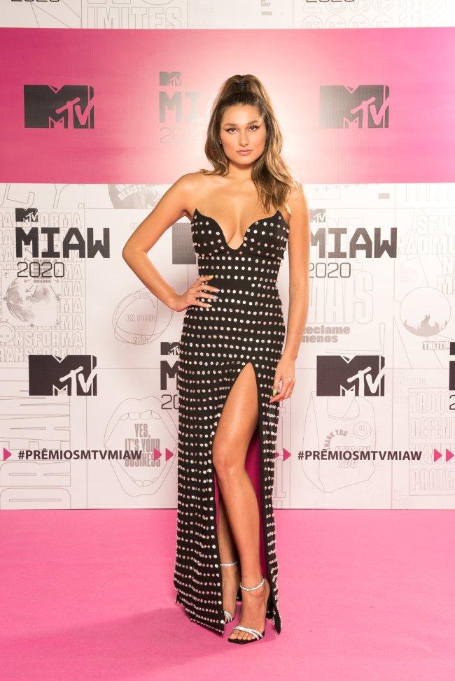 Sasha Meneghel posando no pink carpet do MTV Miaw usando vestido preto com brilhos e uma fenda lateral, ela está com uma mão na cintura e outra ao lado do corpo e sorri levemente