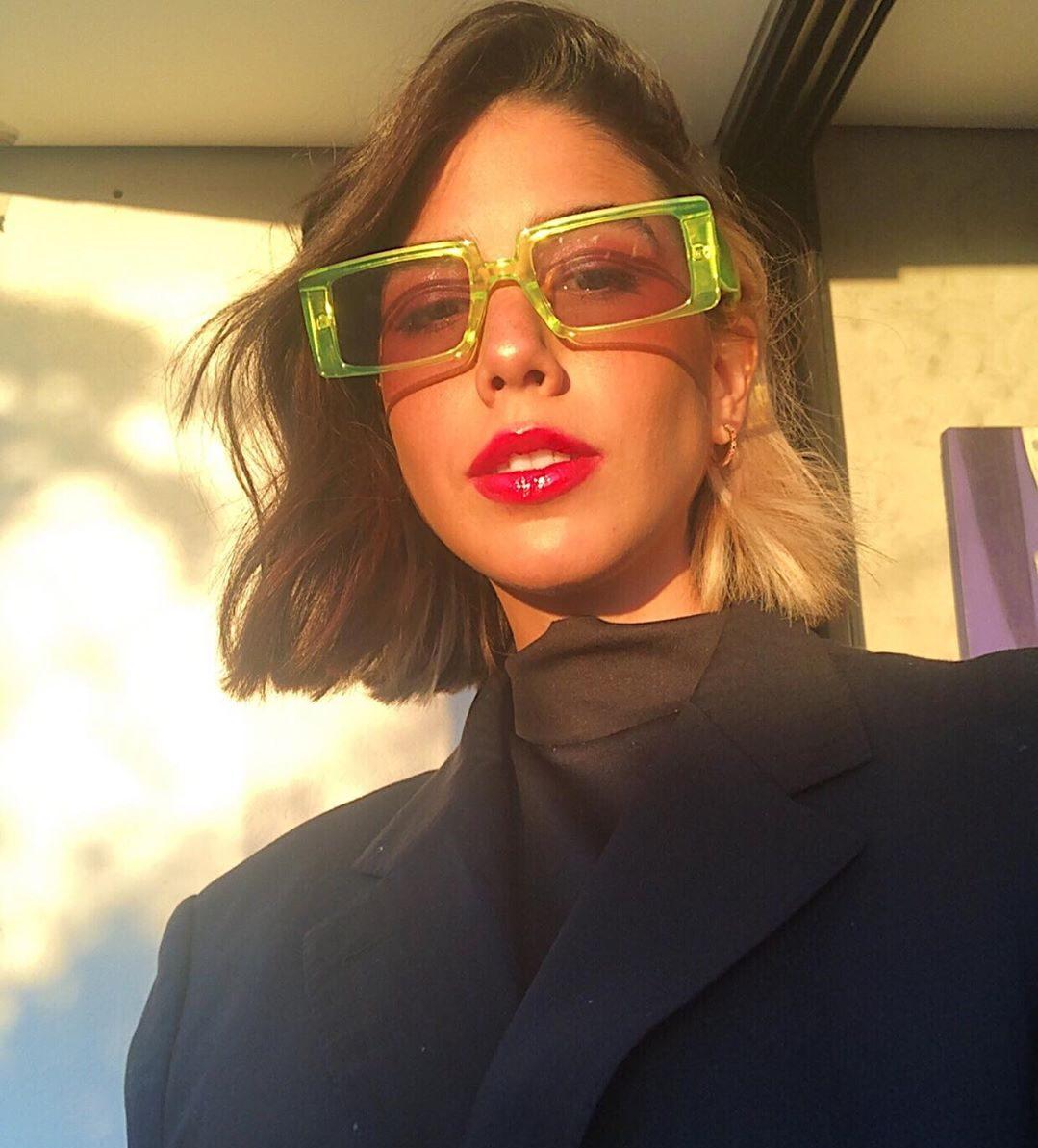 Clara Câmpara usando óculos verdes com blazer preto