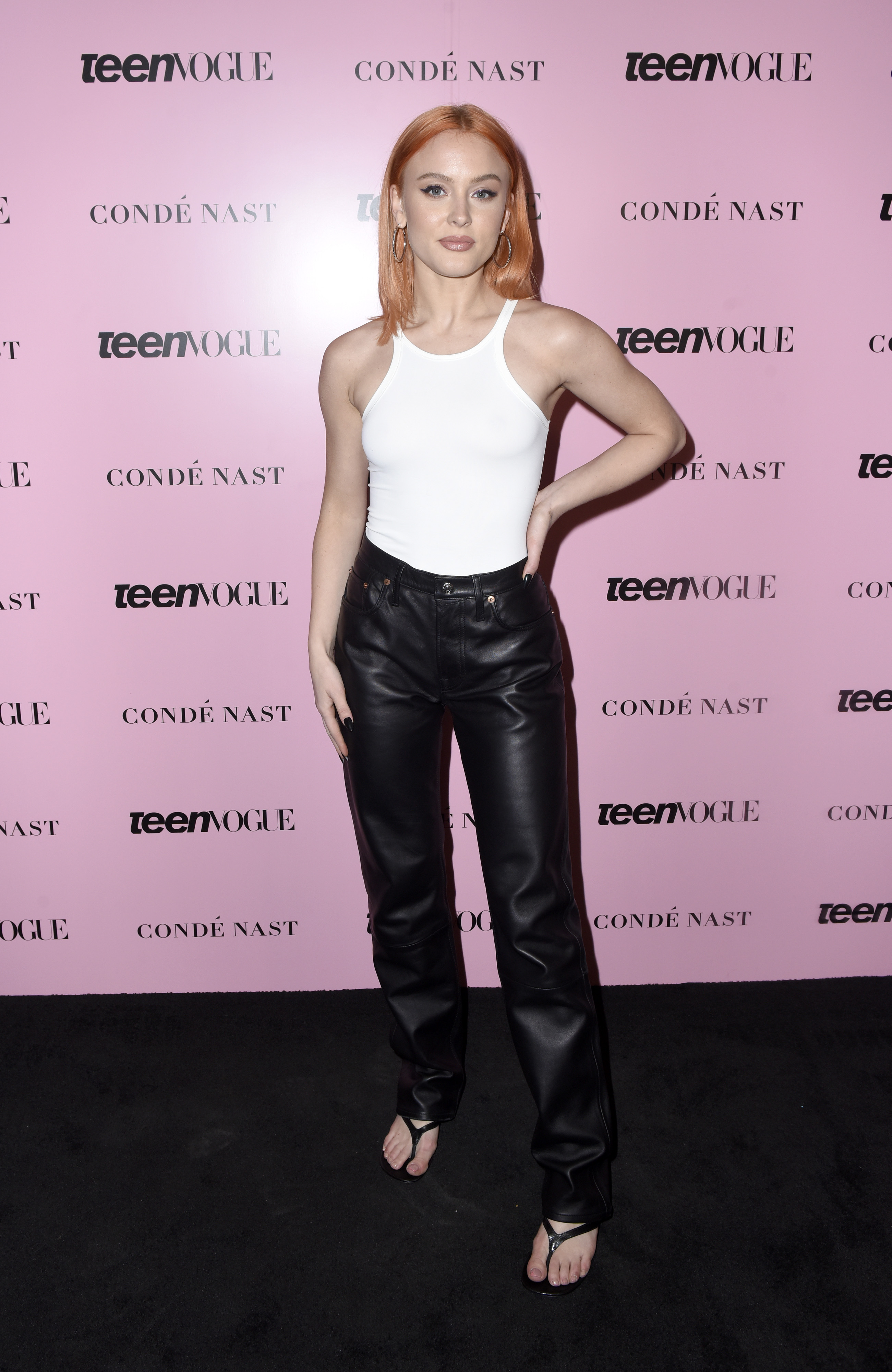 Zara Larsson usando regata branca, calça de couro preta e chinelo de salto preto