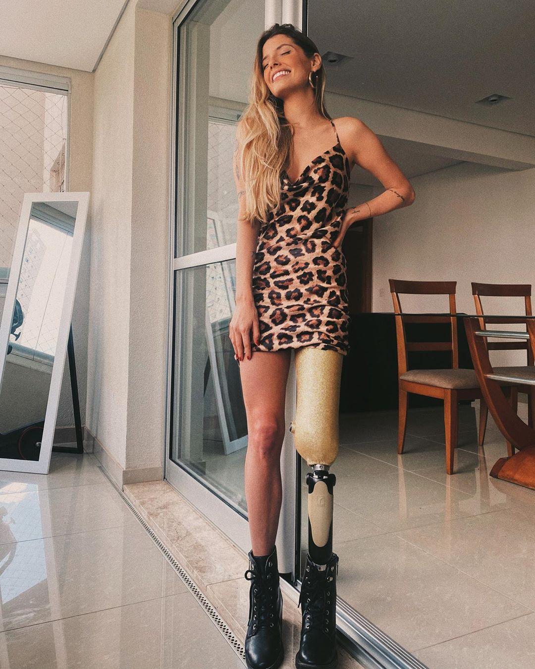 Paola Antonini usando vestido de alcinha com estampa de oncinha e coturno preto. Ela está encostada em uma porta, olhando para o lado, sorrindo com uma das mãos na cintura.
