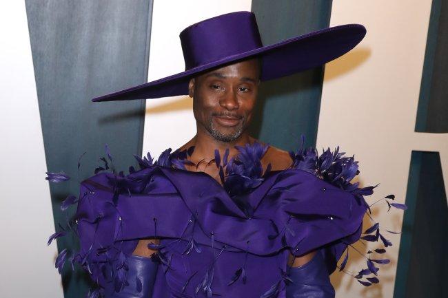 Billi Porter usando um grande chapéu roxo e um vestido roxo