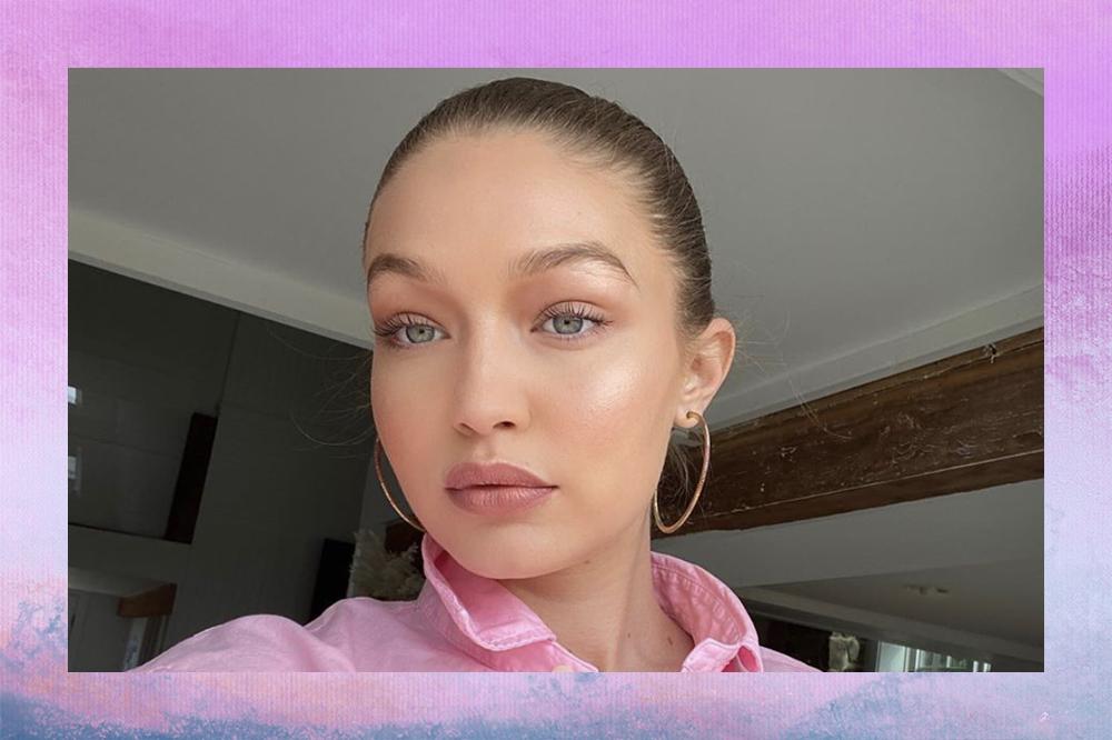 Gigi Hadid em selfie com cabelo preso, brincos de argola e blusa rosa