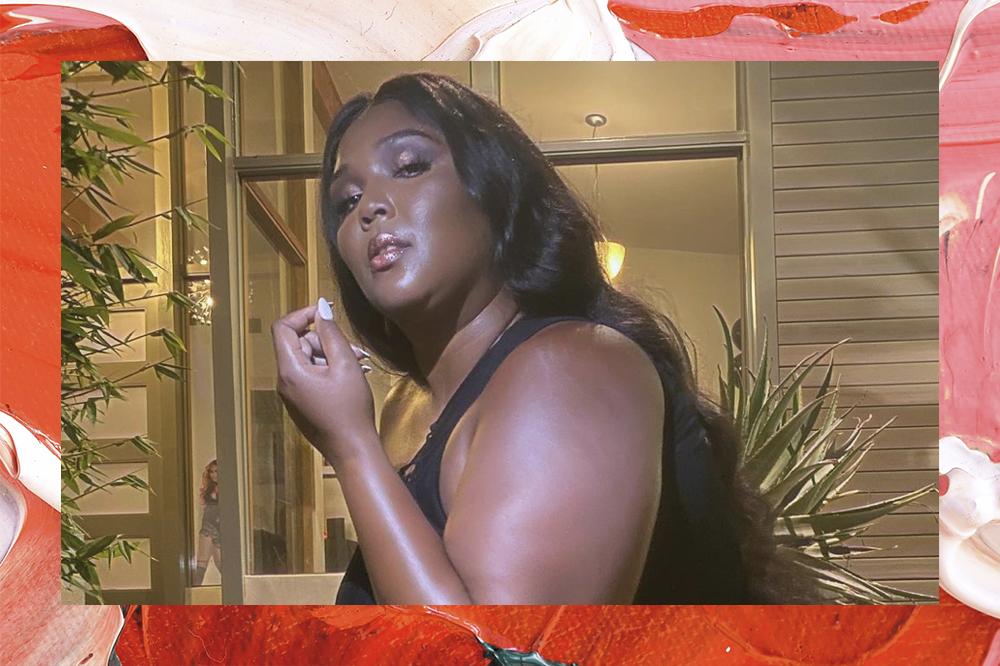 Lizzo posando para foto; a cantora está de lado olhando para câmera com roupa preta e expressão séria, uma de suas mãos está levantada perto do rosto e sua unha está pintada de branco